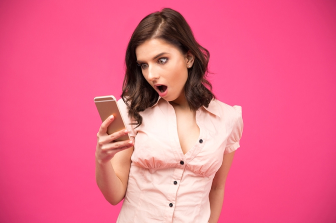 Surprised woman using smartphone